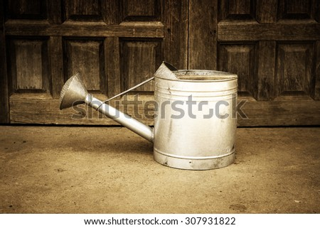 Watering Can Decorated With Wood Doors Background - stock photo