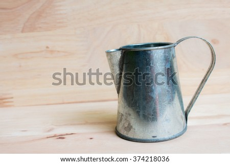 Watering Can miniature wooden background