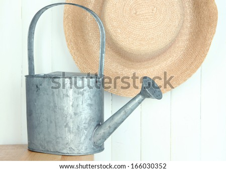 Watering can with hat on wooden background - stock photo