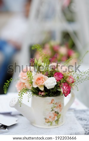 Watering can with roses as decoration on table