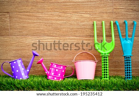 watering cans, pails, fork and rake on green grass with wood background - stock photo