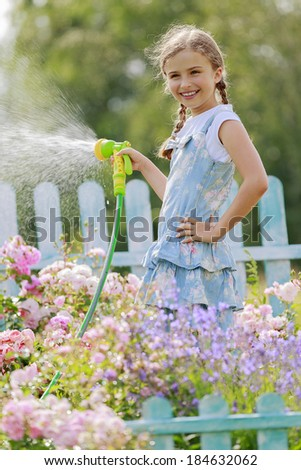 Watering, flower garden - beautiful girl watering roses with garden hose - stock photo