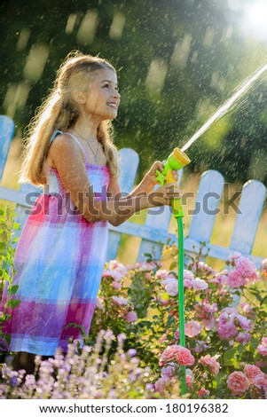 Watering, flower garden - beautiful girl watering roses with garden hose in the garden - stock photo