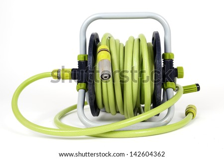 Watering garden hose on the spool isolated on white background - stock photo