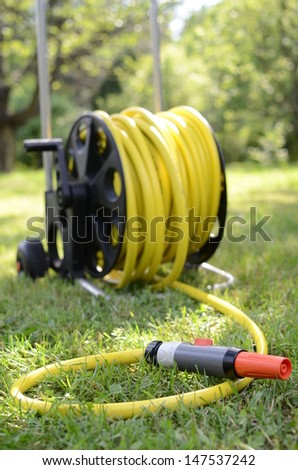 Watering hose on grass in the garden - stock photo