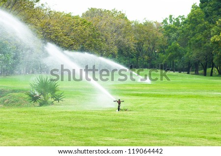 Watering in golf course - stock photo