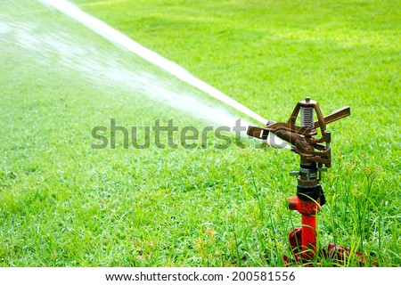 Watering in golf courseWatering turf - stock photo