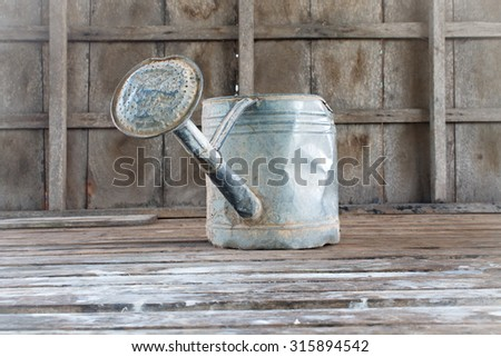 watering pot on lod wooden background - stock photo