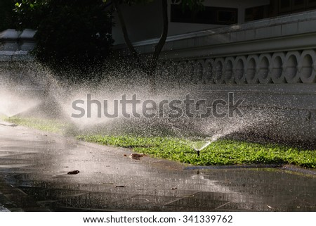 Watering sprinkler on grass field with sunlight at the park - stock photo