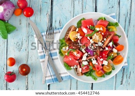 Watermelon and mixed tomato salad with feta cheese, overhead scene on rustic blue wood - stock photo