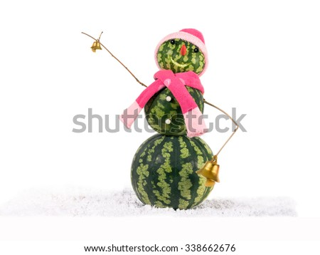 Watermelon christmas snowman with two golden bells in pink hat and scarf at snow. Holiday concept for New Years./Snowman made from watermelon with two golden bells in pink hat and scarf.. - stock photo