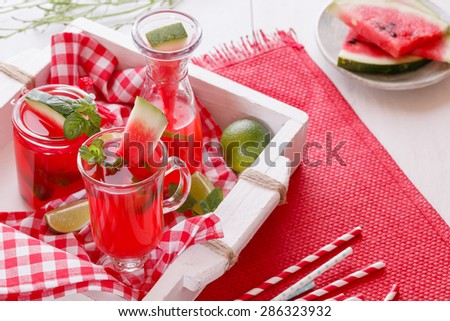 Watermelon cocktails. Freshly made watermelon cocktails and pieces of melon on a rustic wooden tray.  Macro, selective focus, natural light  - stock photo