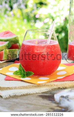 Watermelon drinks outside in the garden with straws and fresh mint. Also available in horizontal.  - stock photo