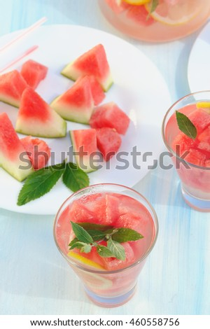 Watermelon drinks with straws, lemon and fresh mint  outside in the garden