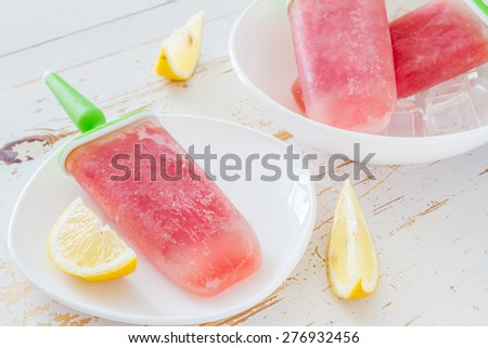 Watermelon fruit ice pops on white plate, white wood background - stock photo