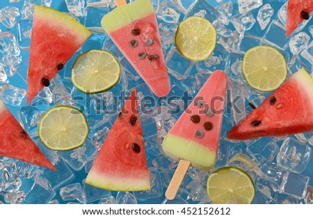 Watermelon, fruit  popsicle and lime slices on ice cubes - stock photo