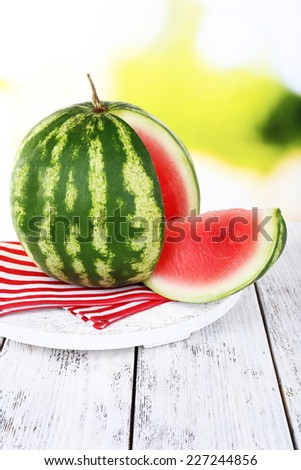 Watermelon on napkin on stand on wooden table on natural background - stock photo