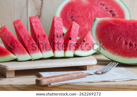 Watermelon on wooden table over grunge background - stock photo