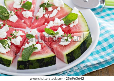Watermelon pizza with crumbled feta cheese and herbs - stock photo