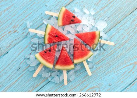 watermelon popsicle yummy fresh summer fruit sweet dessert on vintage old wood teak blue flat lay - stock photo