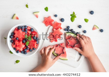 Watermelon salad. Slices of watermelon in the shape of a star. Children's hands cooking fruit salad on white table. Top view, flat lay - stock photo