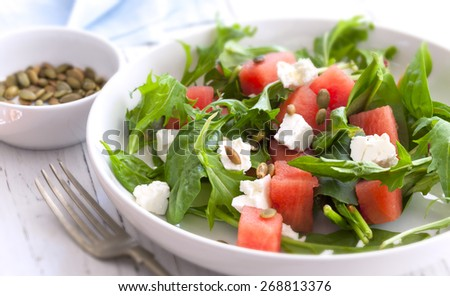 Watermelon salad with feta cheese, toasted pumpkin seeds, arugula, spinach and mint. - stock photo