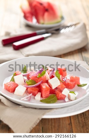 Watermelon salad with feta, mint and red onion. On wooden rustic table. - stock photo