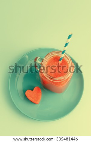 Watermelon shake in Mason jar with lime, straw and heart shaped watermelon slice on blue plate