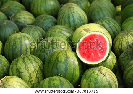 watermelon slice.Many big sweet green watermelons and one cut watermelon.