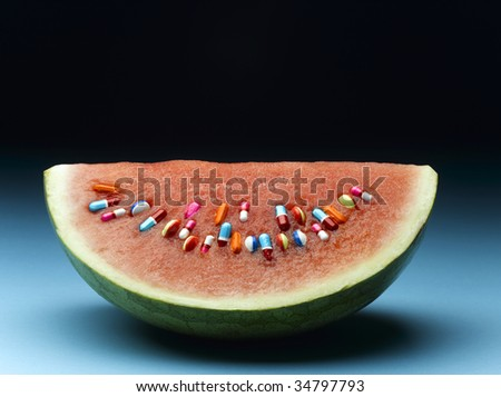 Watermelon with pills in place of seeds - stock photo