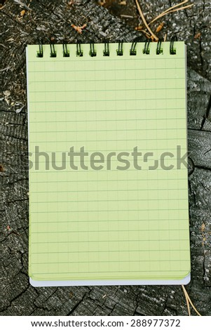 waterproof notebook lying on a wooden stump in the forest