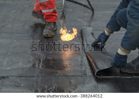 waterproofing roll bituminous material in the trench. construction worker manufacturer uses a gas burner propane tank fire.