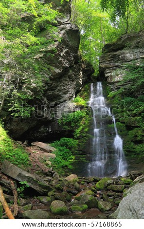 Waters falls from a cleft in the rocks from the forest above at Buttermilk Falls in the Catskills Mountains of New York - stock photo