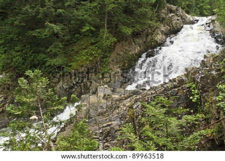 Waters sprays as water churns through the forest at Lower Split Rock Falls in the Adirondack Mountains of New York - stock photo