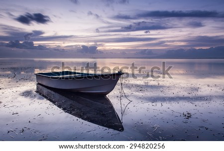 Waterscape at dusk with boats and seaweed and beautiful clouds in the background at low tide