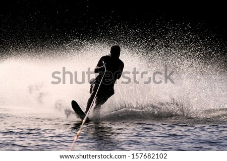 Waterskier silhouette with glowing spray - stock photo
