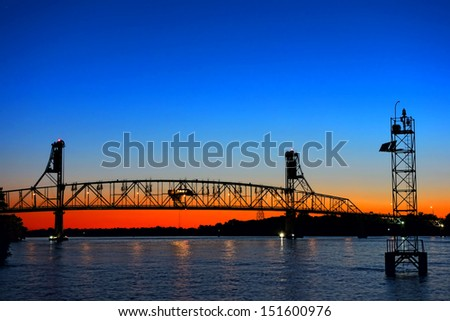Waterway crossing auto transportation steel truss bridge with lift span over the Delaware River between New Jersey and Pennsylvania at dusk with spectacular evening sky  - stock photo