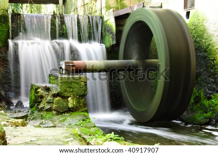 Waterwheel and waterfall - stock photo
