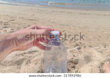 Watter bottle opening on a hot summer day at the beach - stock photo