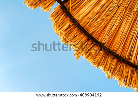 Wattled straw beach umbrella on clear blue sky background. Outdoors summertime multi colored closeup horizontal image. View from below. - stock photo