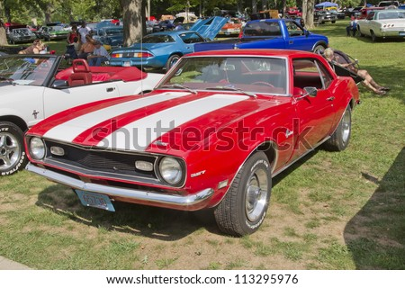 WAUPACA, WI - AUGUST 25: Red White Chevy Camaro 327 car at the 10th Annual Waupaca Rod & Classic Car Club Car Show on August 25, 2012 in Waupaca, Wisconsin. - stock photo