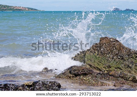 Wave and splashes on beach - stock photo