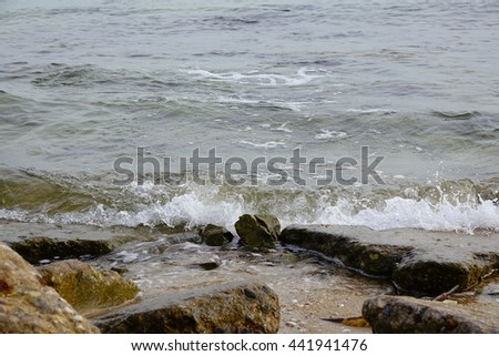 wave and stone on beach at the sea,select focus with shallow depth of field:ideal use for background.