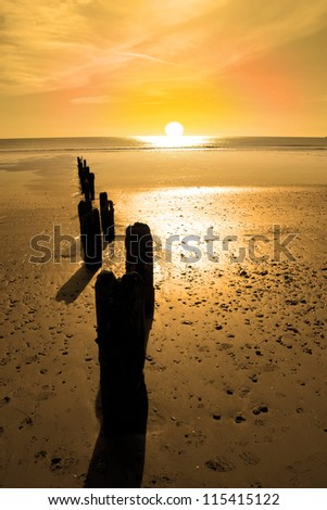wave breakers at sunset on a golden beach in youghal county cork ireland - stock photo