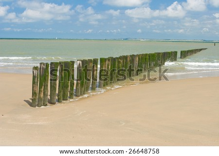 Wave breakers on a Dutch beach in day - stock photo