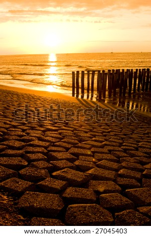 Wave breakers on a Dutch beach in sunset - stock photo