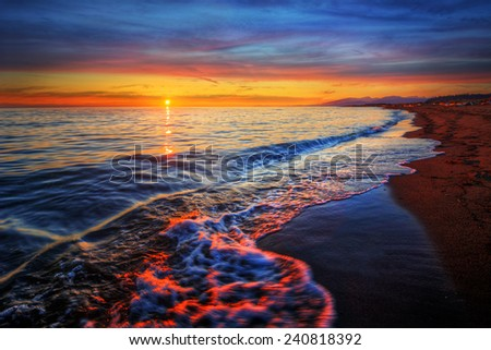Wave breaking onto sandy beach at tranquil sunset - stock photo