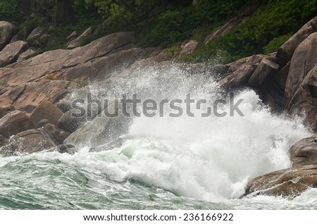 Wave crashing against stones at the rocky beach - power of nature