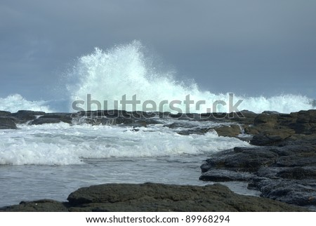 Wave crashing against the rocks at an ocean beach - stock photo