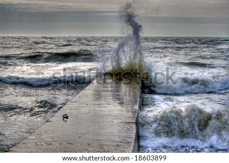 Wave crashing on breakwater - stock photo